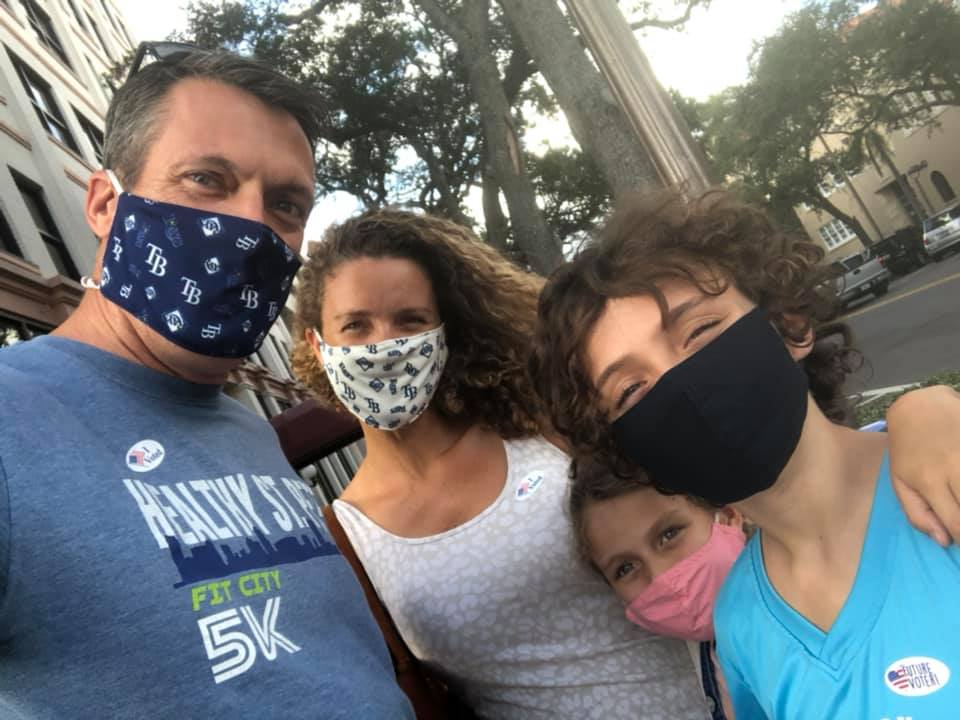 A family of four in face masks pose for a selfie.