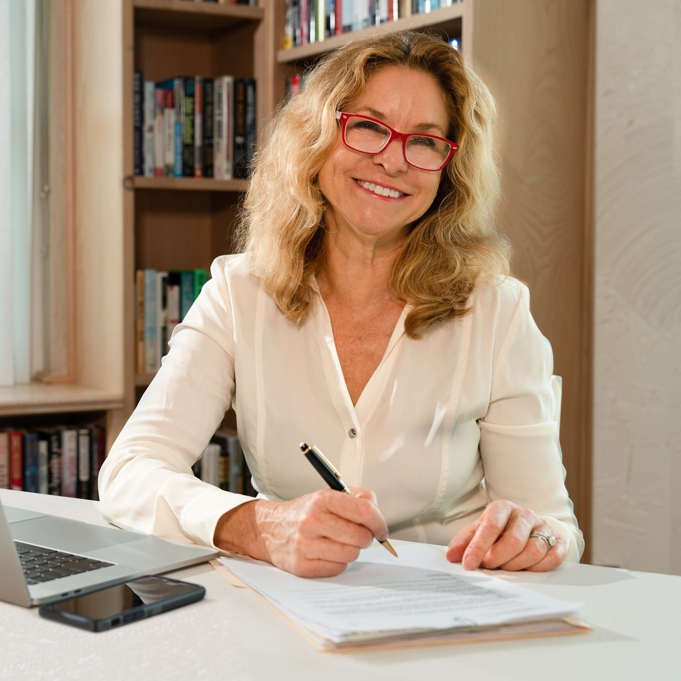 A woman in red glasses and a white blouse sits at a desk with a laptop, holding a pen over a piece of paper, smiling at the camera.