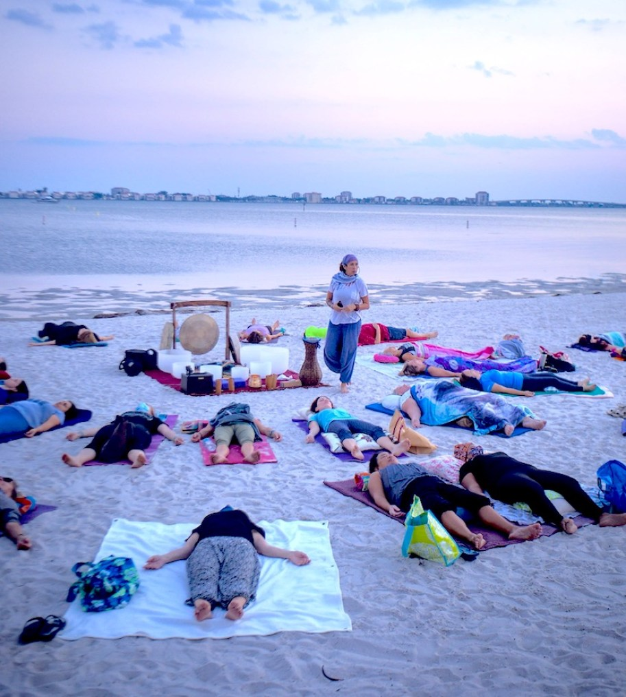 On a beach at sunset, a woman stands at the center of a group of people lying on yoga mats, with a large gong.