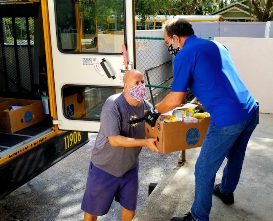 A man in a blue shirt and jeans lowers a box down to a man in a face mask and purple shirt at the back of a yellow school bus.