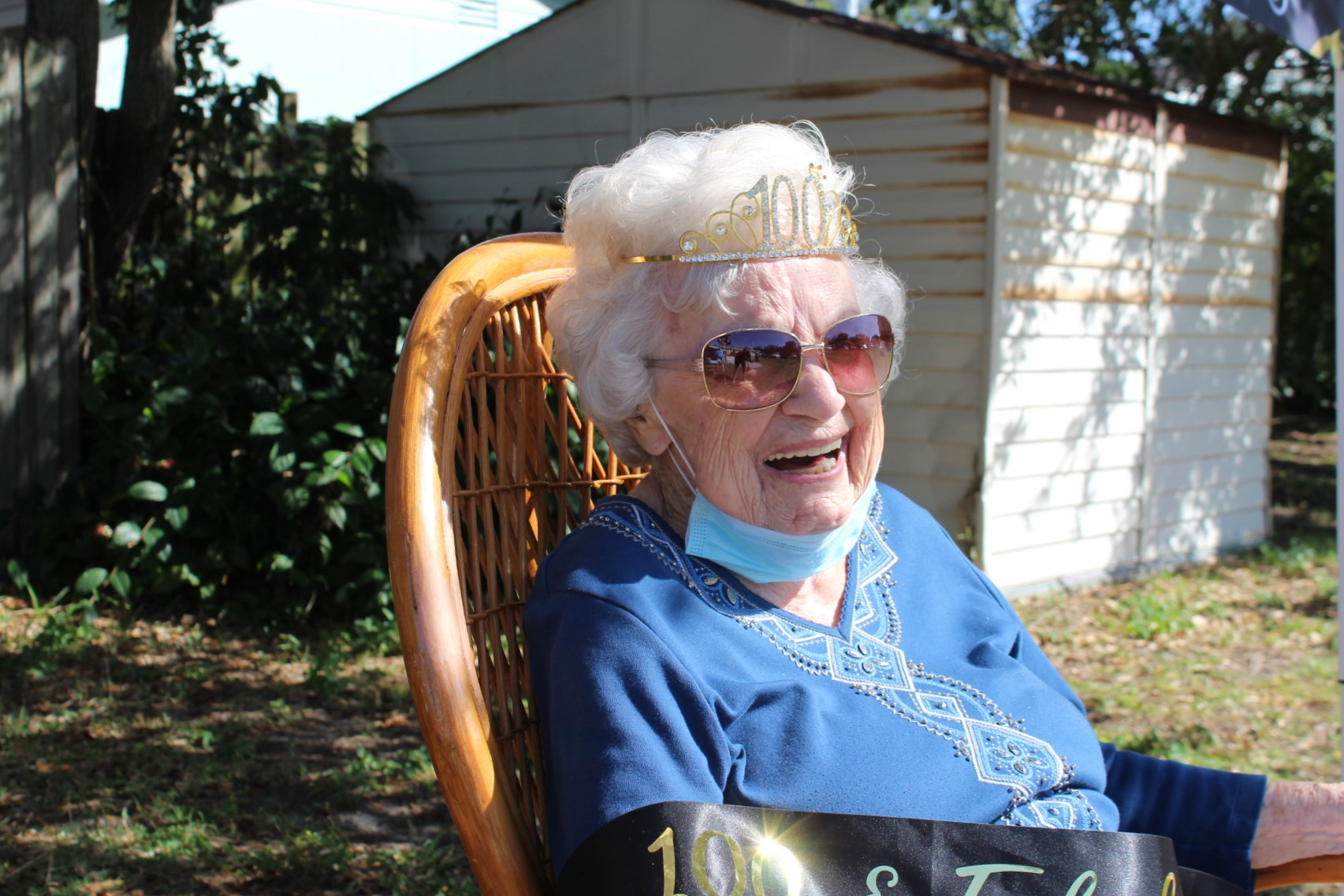 An older lady with white hair and sunglasses sits in a chair with a blue shirt and tiara.
