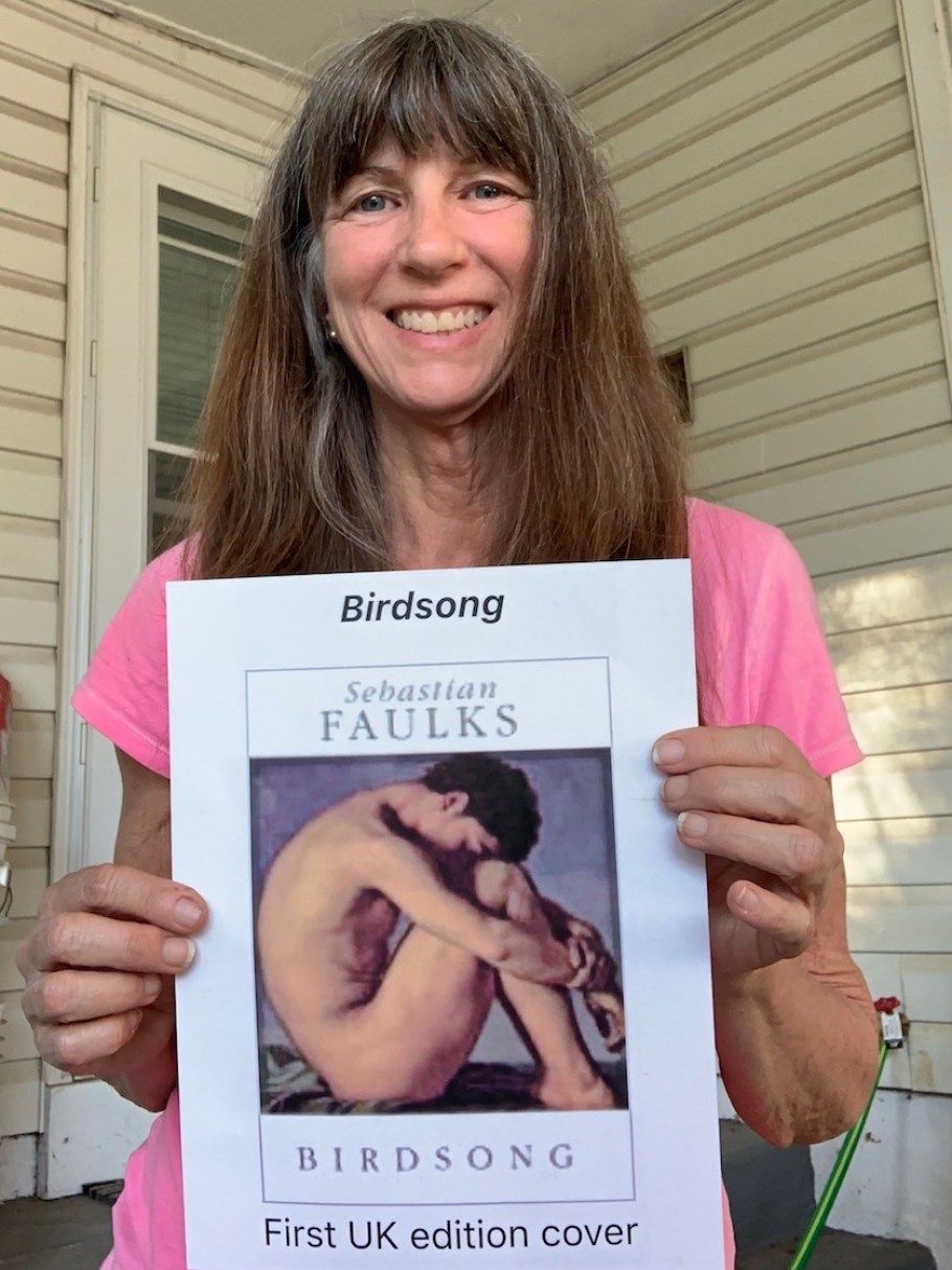 "A woman in a pink shirt holds up a book. The cover is white with an image of a nude figure and says ""Birdsong"" by Sebastian Faulks"