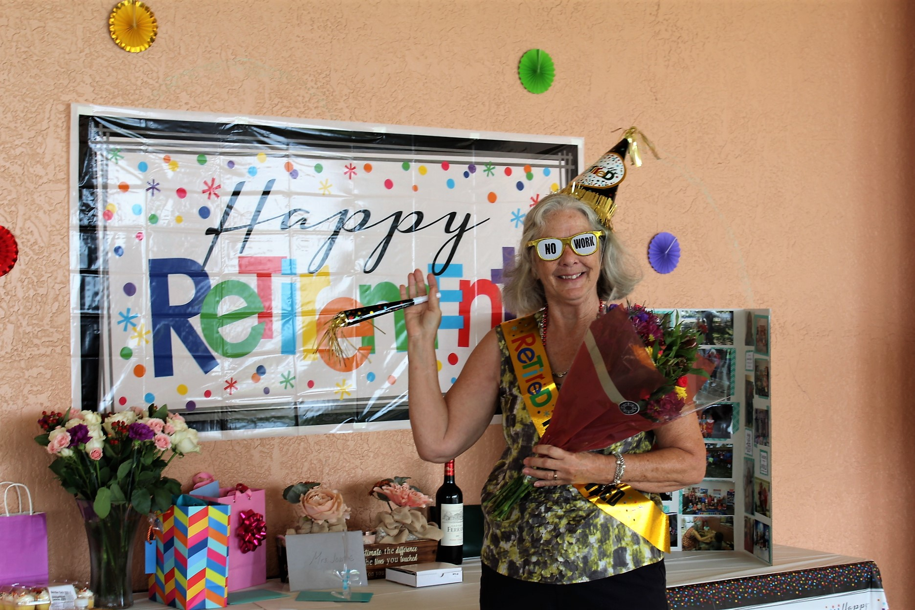 "A woman in party hat and glasses celebrates in front of a ""Happy Retirement"" sign."