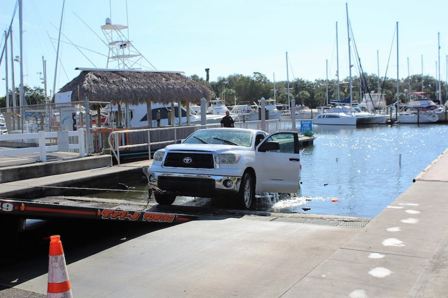 A white Toyota truck partially submerged in the water at a marina boat dock.