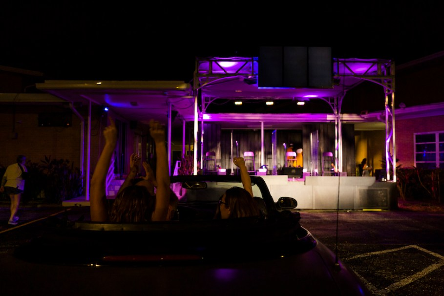 A night time shot of people in a car looking at a stage set up for a drive-through performance.