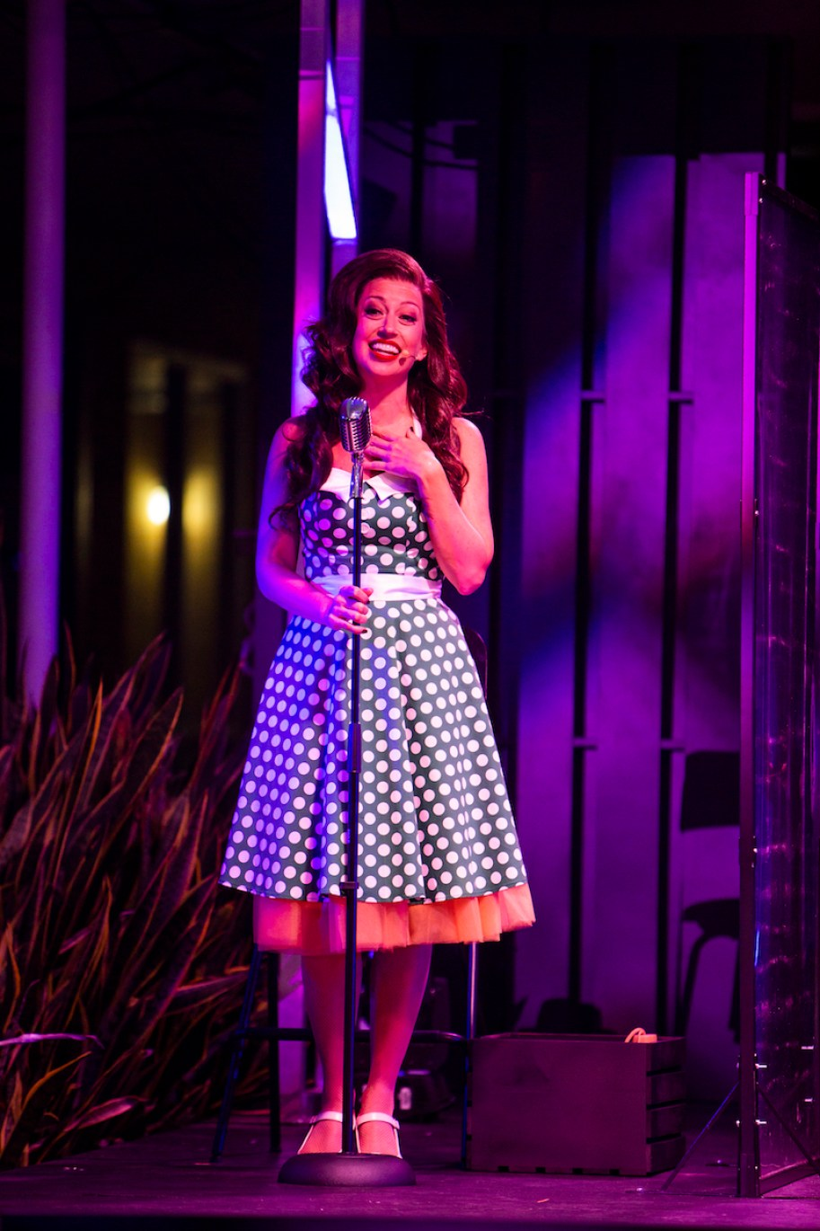 A woman on a stage in front of a microphone in a blue polka dot dress and 1940s hairdo.
