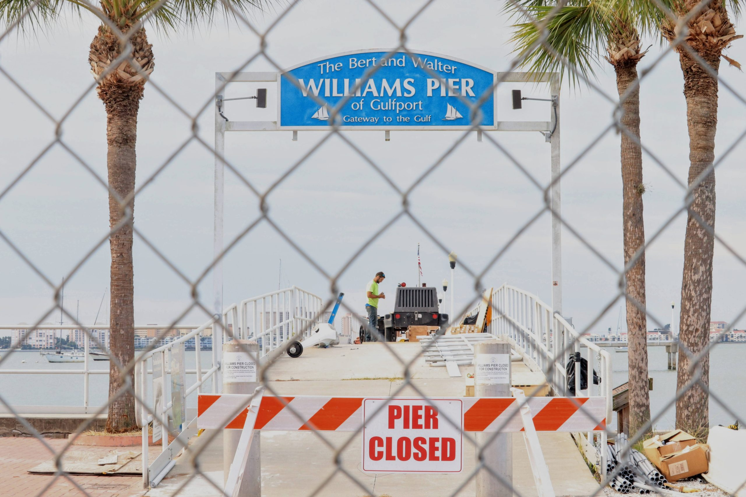 A photo of a pier through chain link fence with a sign Bert and Walter Williams Pier and another sign that reads Pier Closed