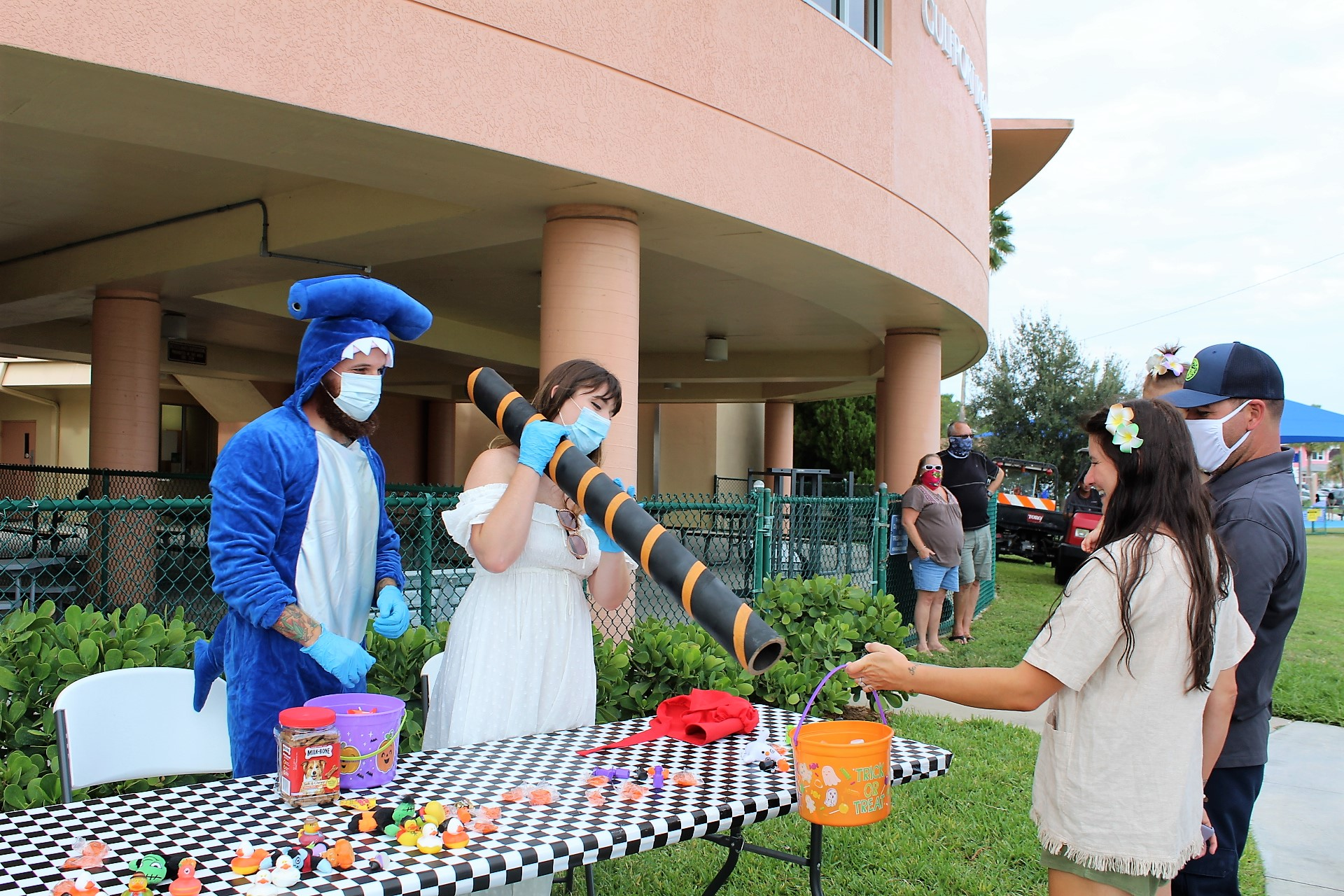 A couple in Halloween costumes puts out a chute for candy at an outdoor event.