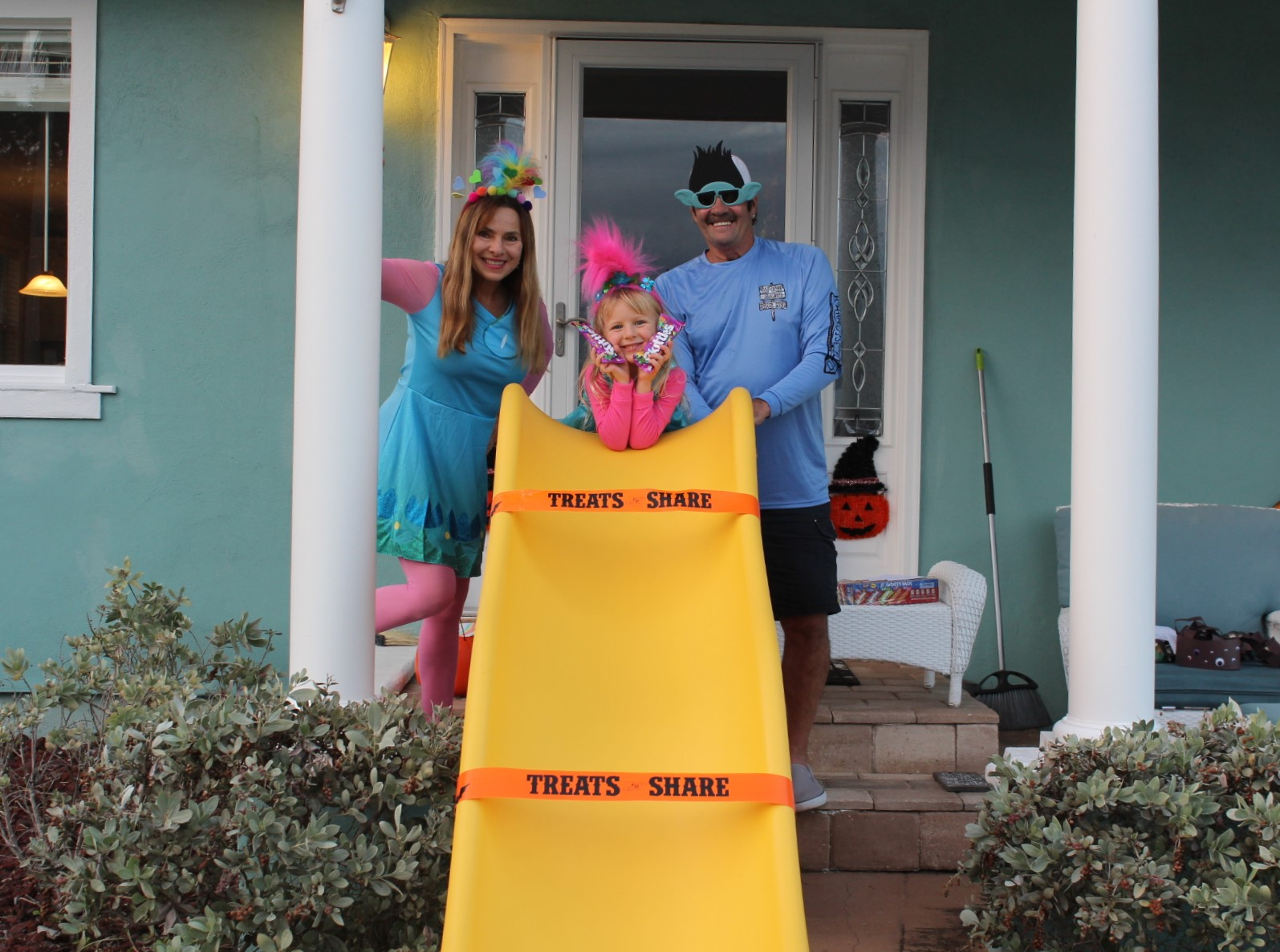 A man and woman with a child in front of a yellow slide on a front porch.