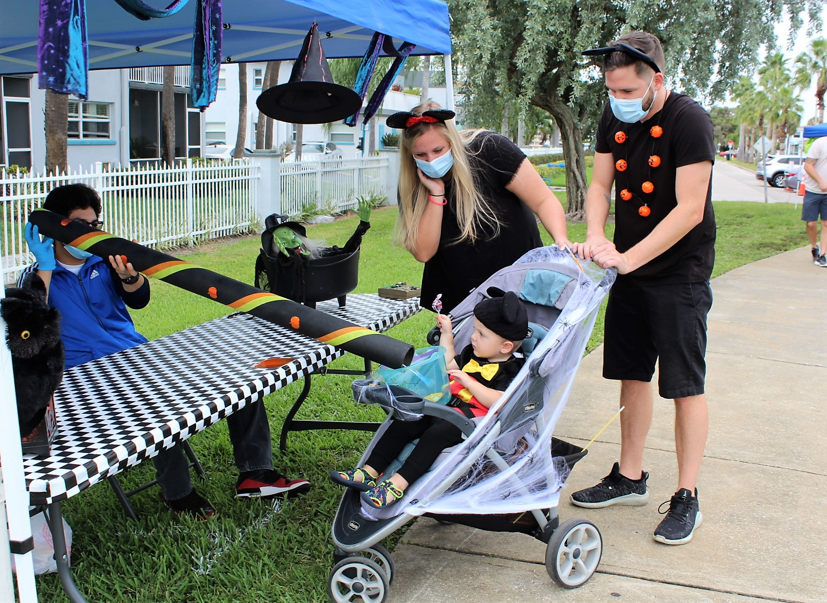 A mand and a women dressed in black with face masks and a small child in a blue stroller at a Halloween booth.