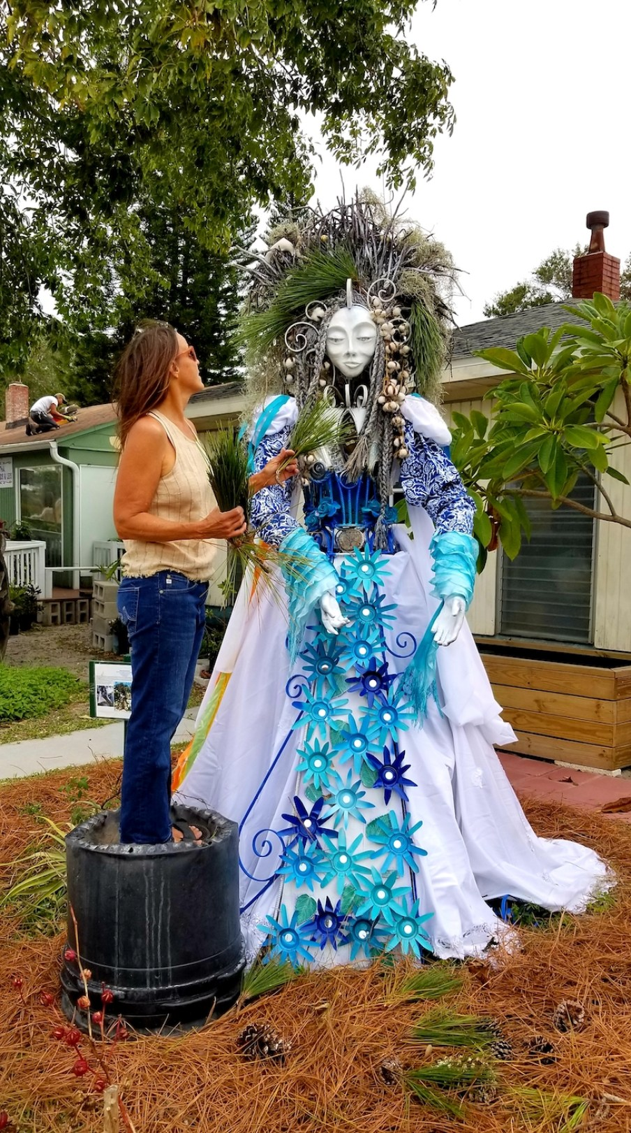 A woman decorating a tall human statue with holiday decor.
