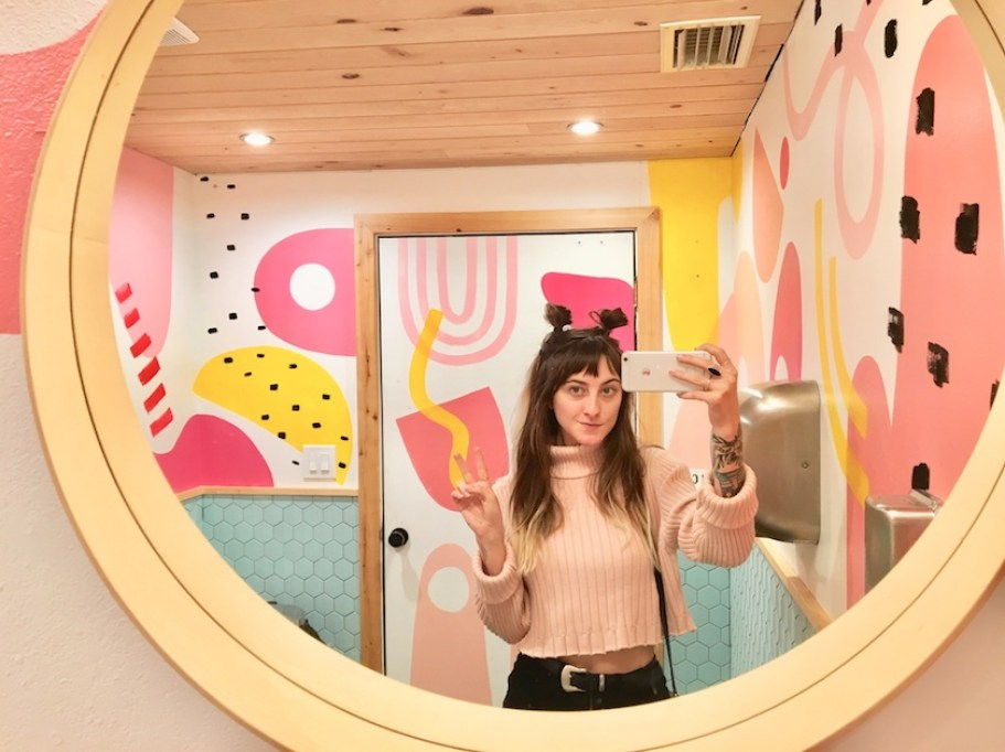 A woman taking a selfie in a mirror with a pink mural theme on the walls.