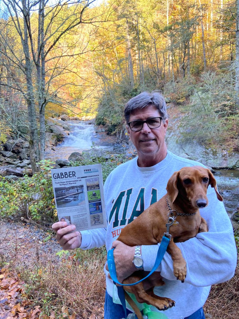 A man holding a brown dog and a Gabber Newspaper stands in a fall forest in front of a waterfall.