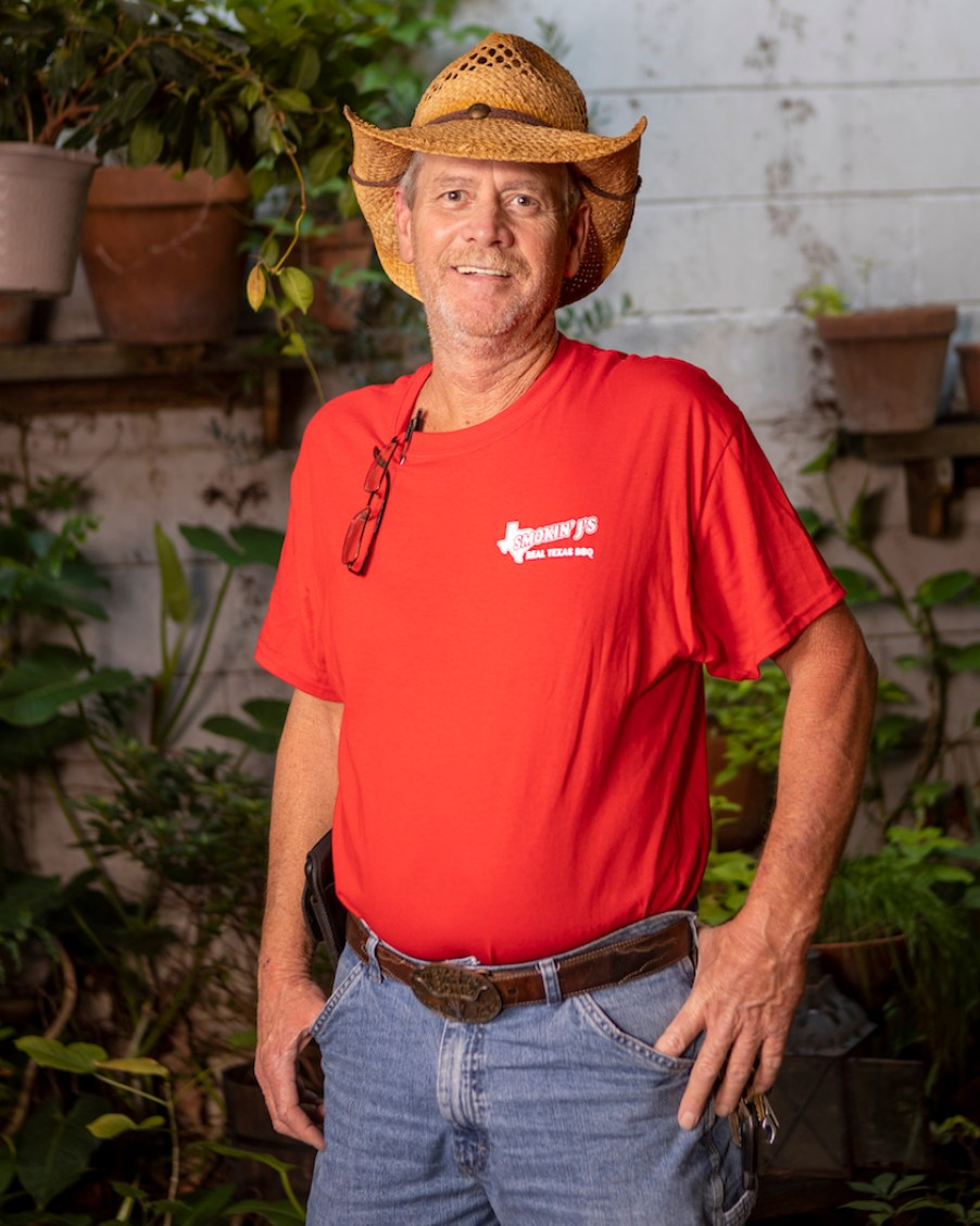 A man in a straw cowboy hat and a red shirt