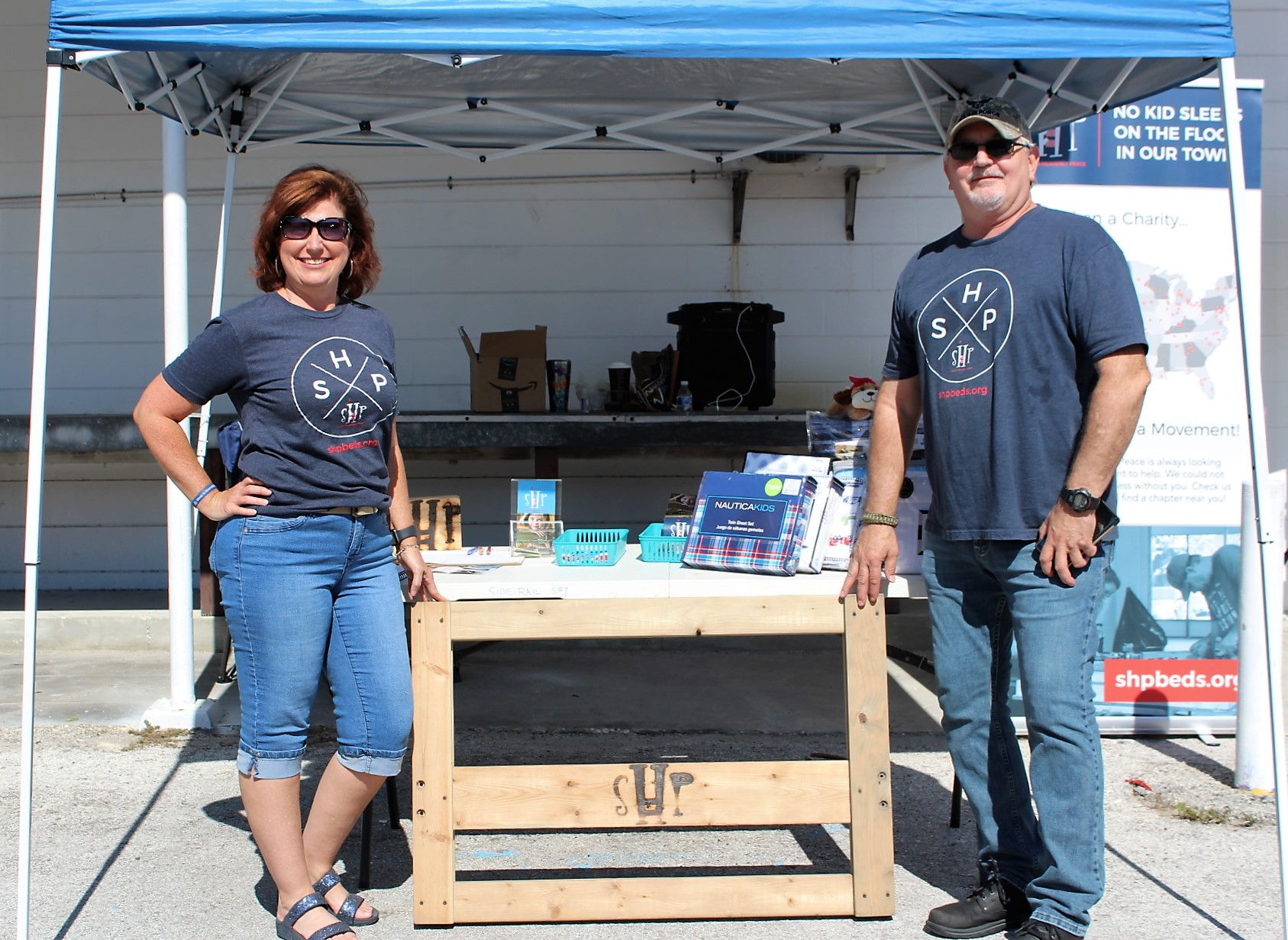Two people in blue shirts stand on either side of a table outside in the sun.