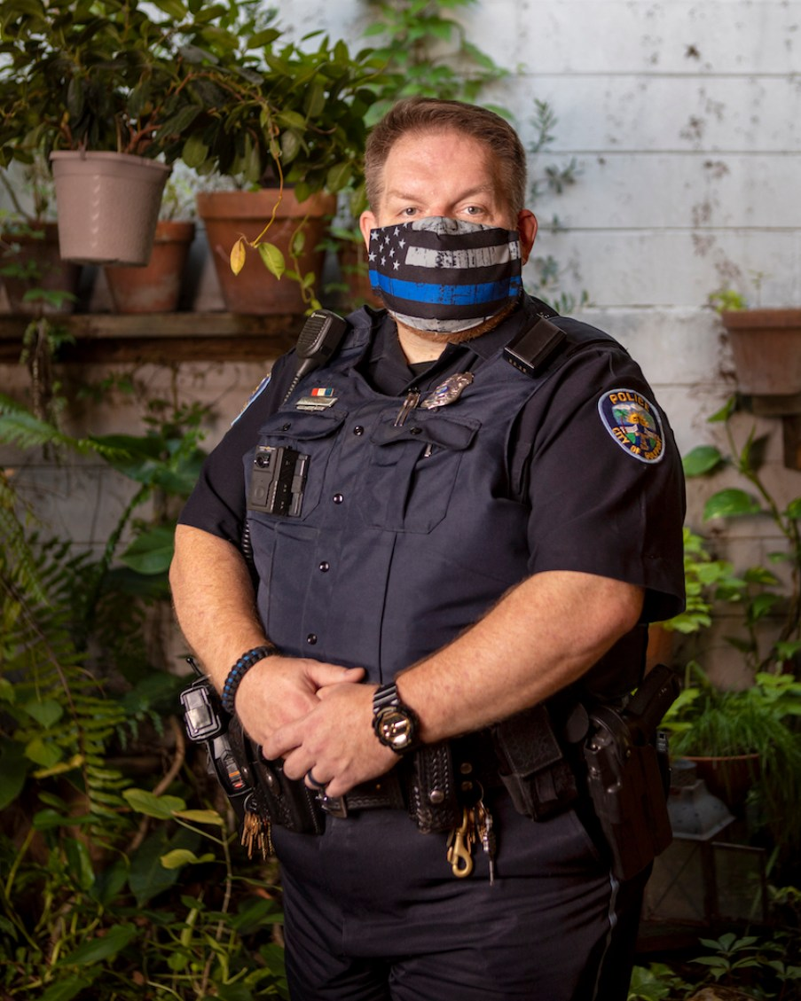 A police officer in a black uniform and a face mask.