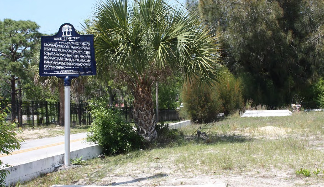 A historical marker in a sandy lot with a palmetto tree