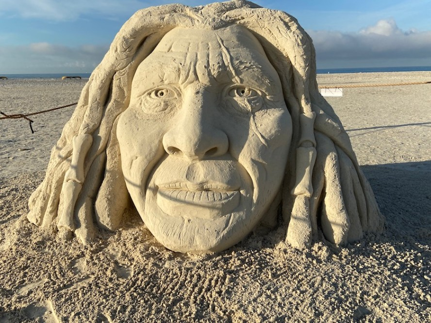 A sand sculpture of a large human head with long hair