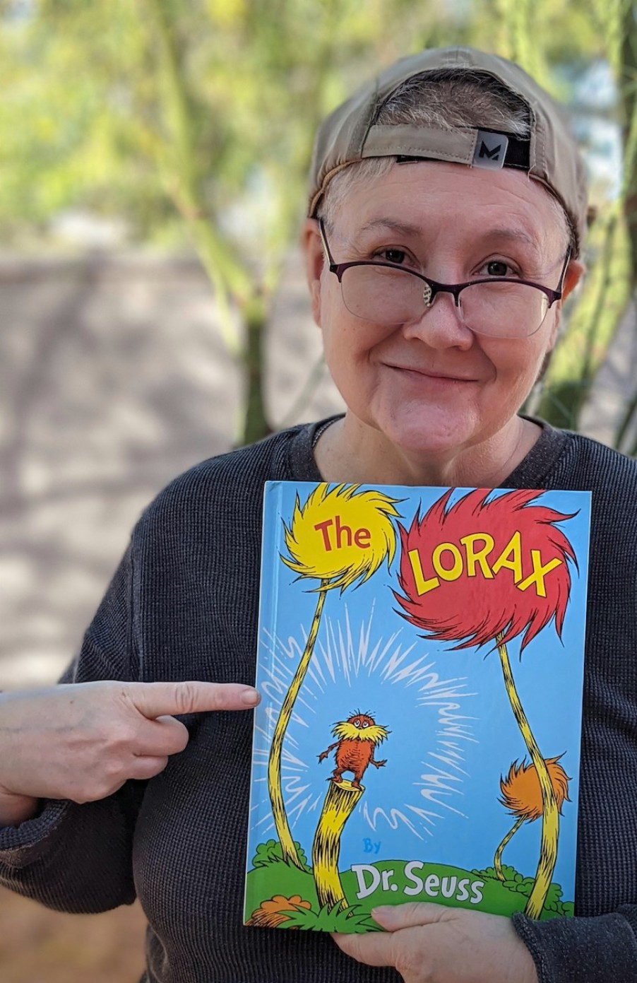 """A woman in glasses looking at the camera and holding a book """"The Lorax"""" by Dr. Suess."""