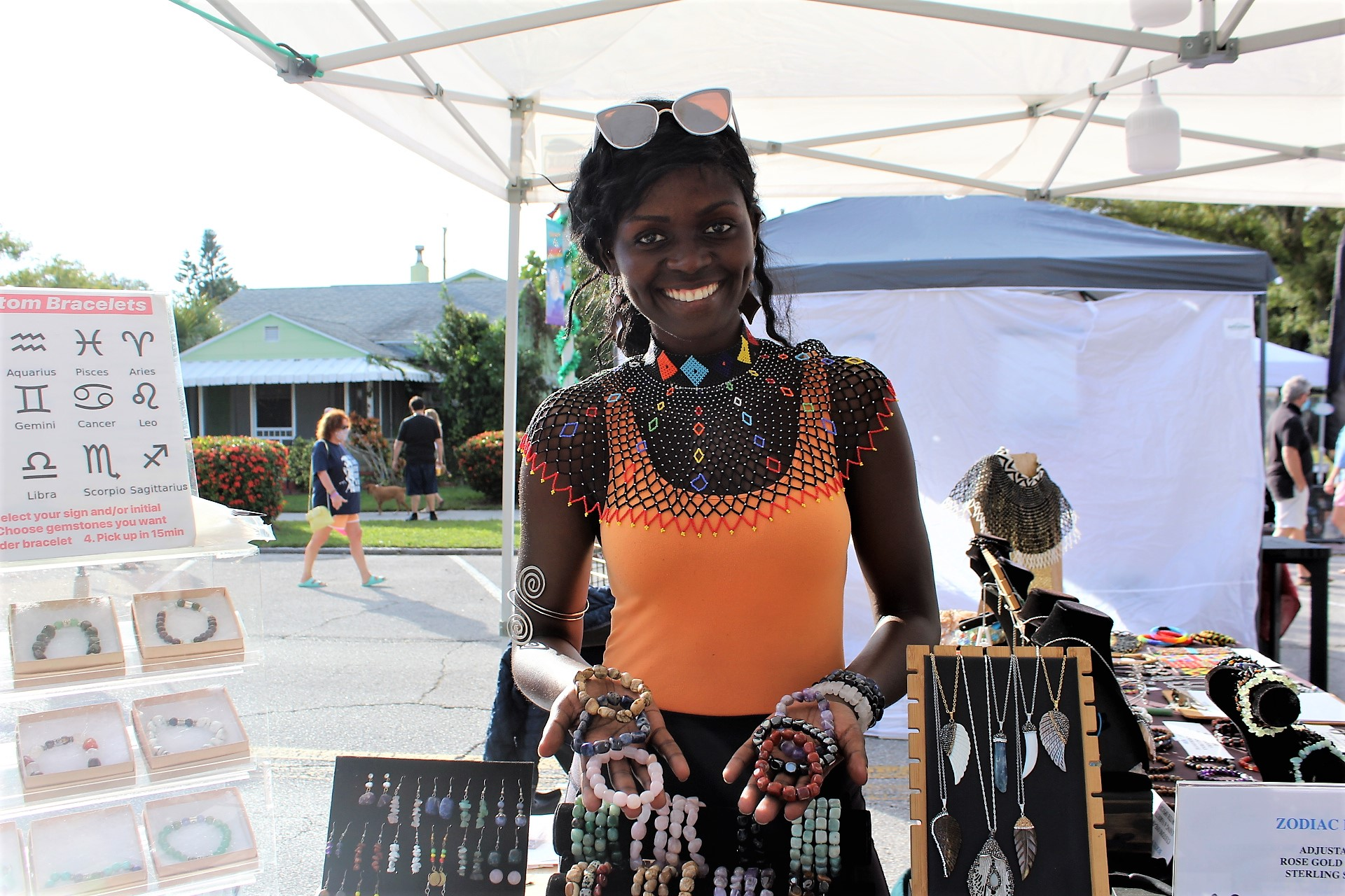A woman in an orange tank top outside at a jewelry stall.