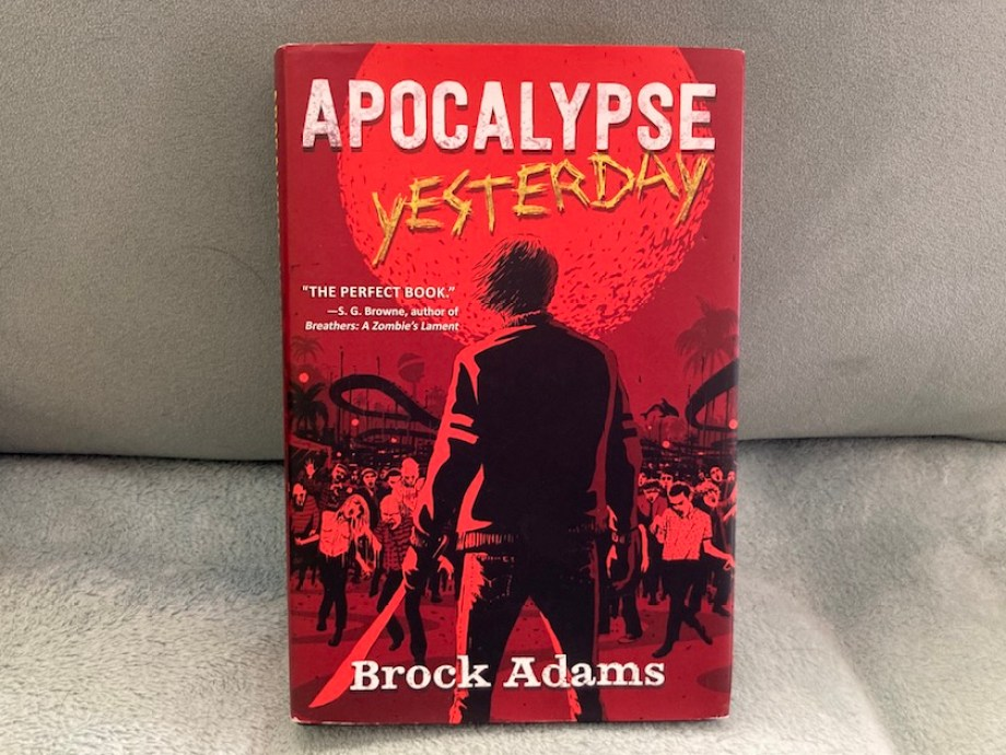 "A photo of a cover of a book titled ""Apocalypse Yesterday."" It is red with zombie imagery."