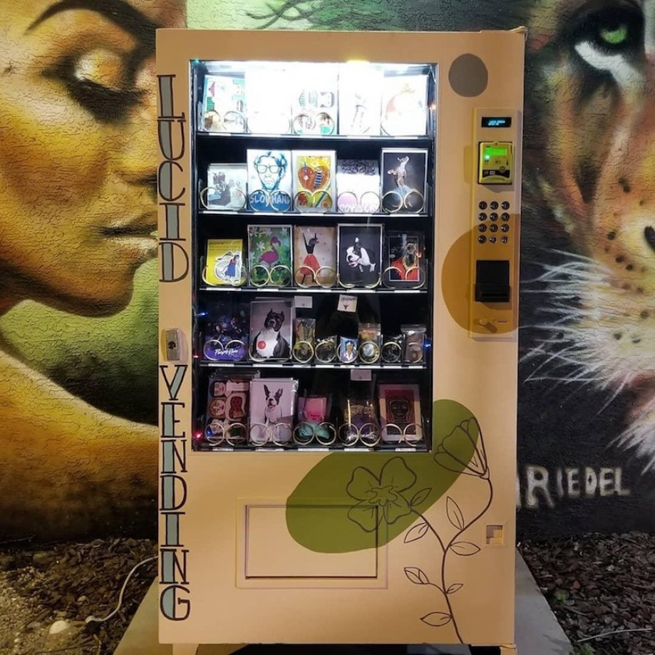 A vending machine that has art and gifts in it, in front of a mural of a woman and a tiger.