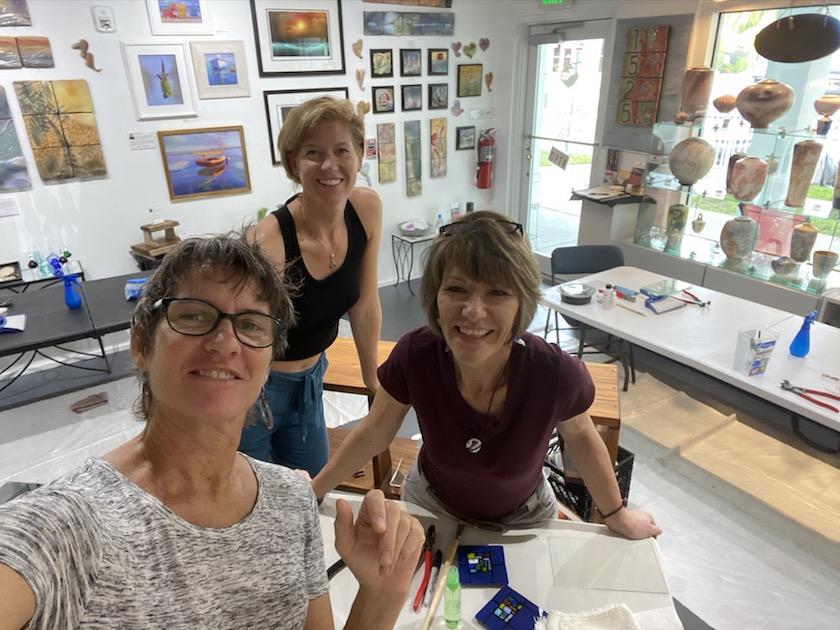 Three women posing for a selfie in an art studio