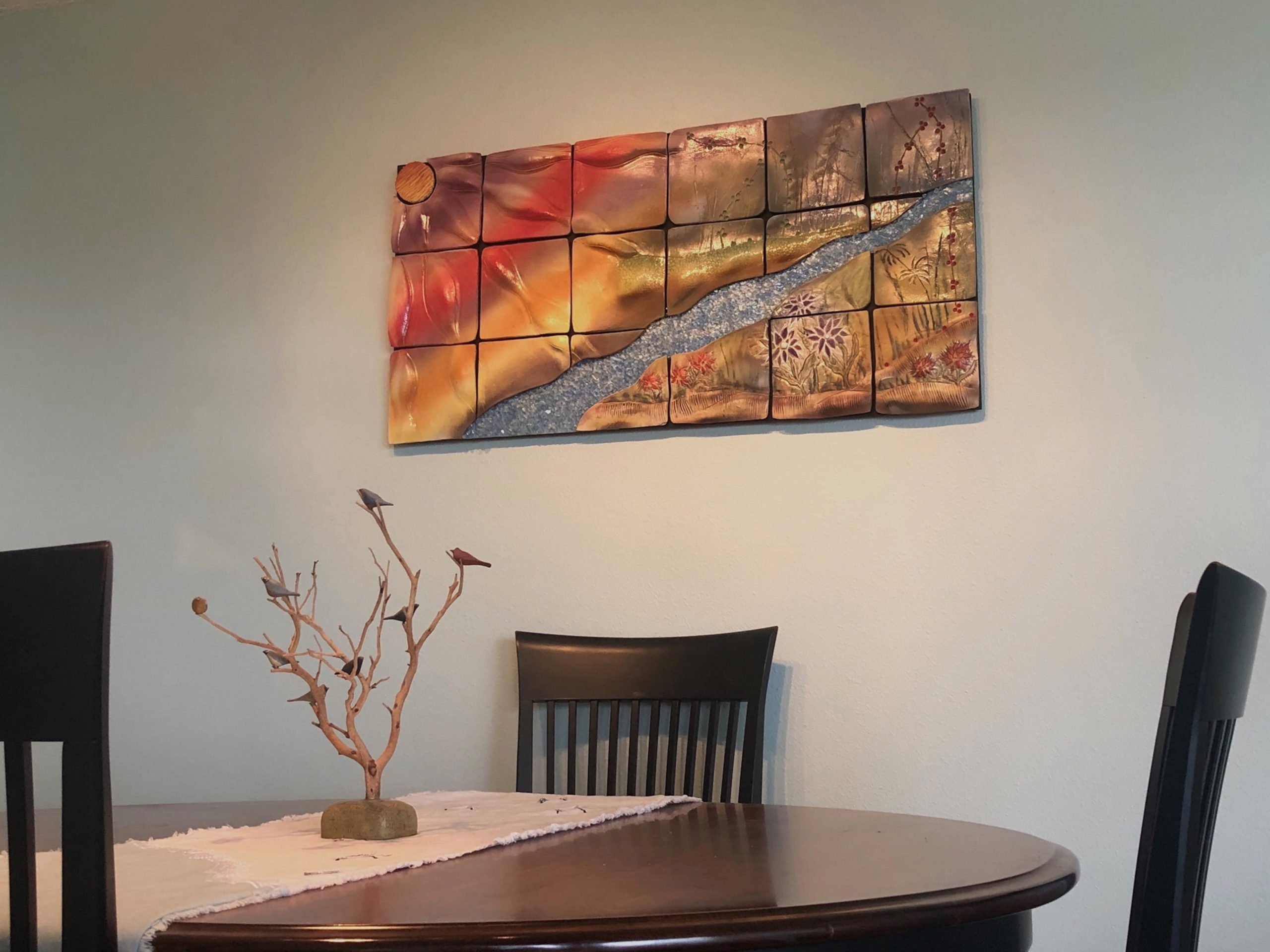 A ceramic wall piece over wooden table and chairs