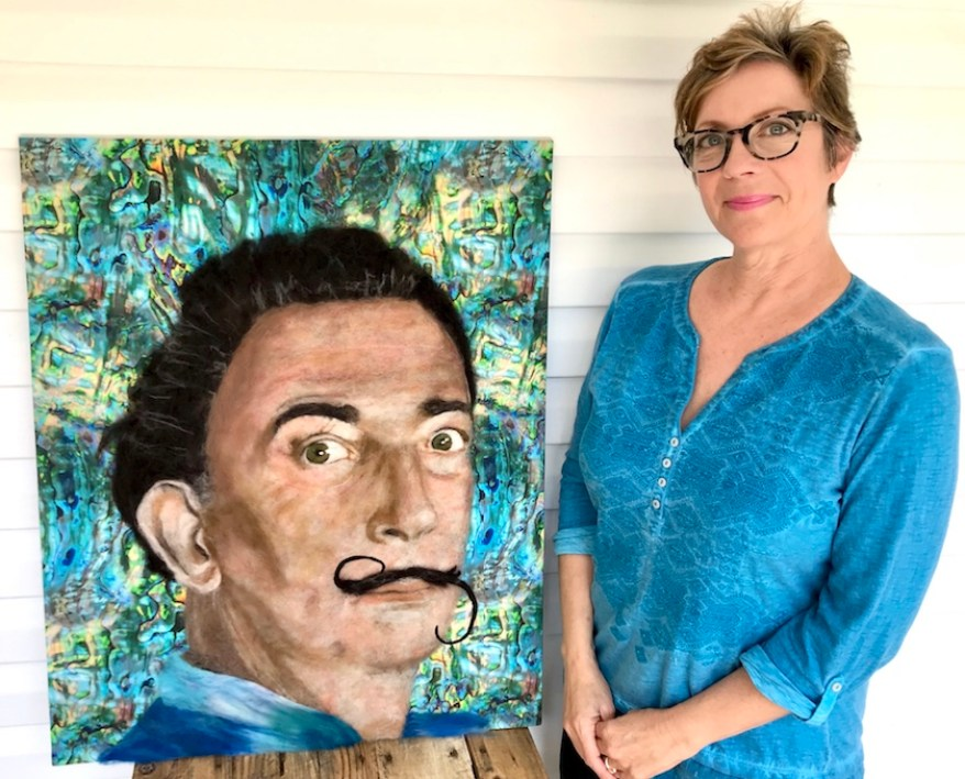 A woman in a blue shirt and glasses stands next to her portrait of Salvador Dali.
