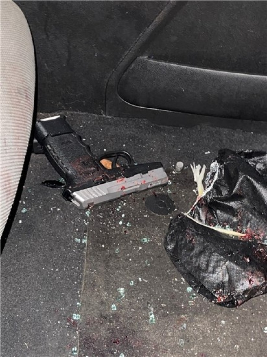 The floor of a car with a handgun and debris and a black plastic bag.