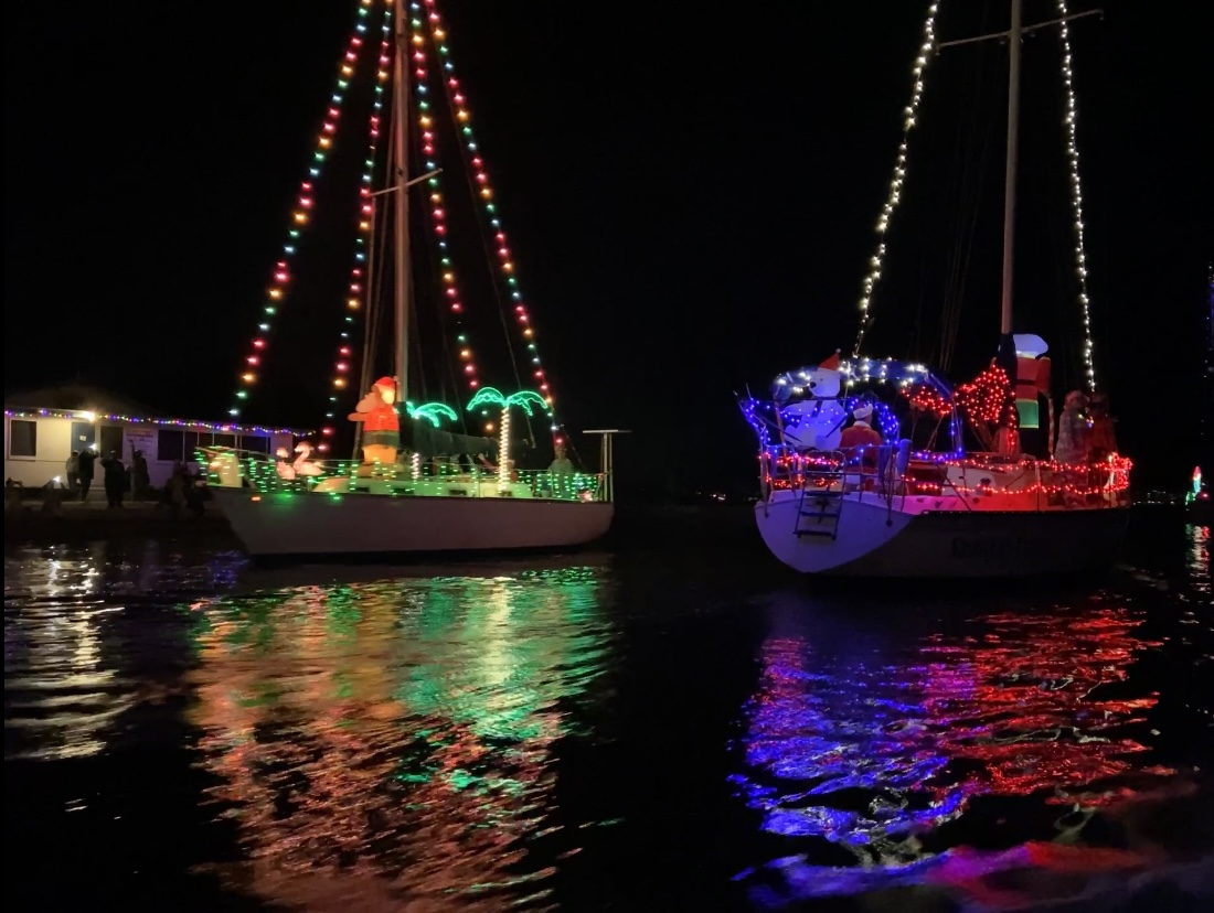 Boats decorated with Christmas lights on the water at night