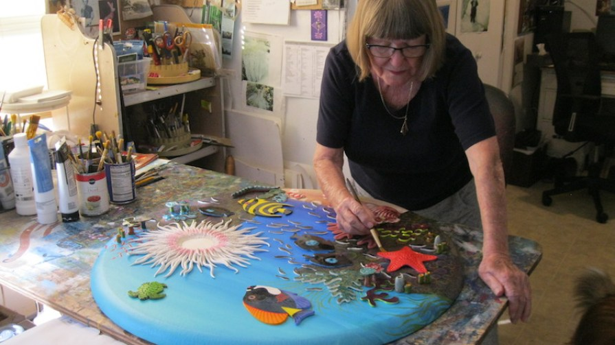 A woman working in an art studio on a beach scene painting.