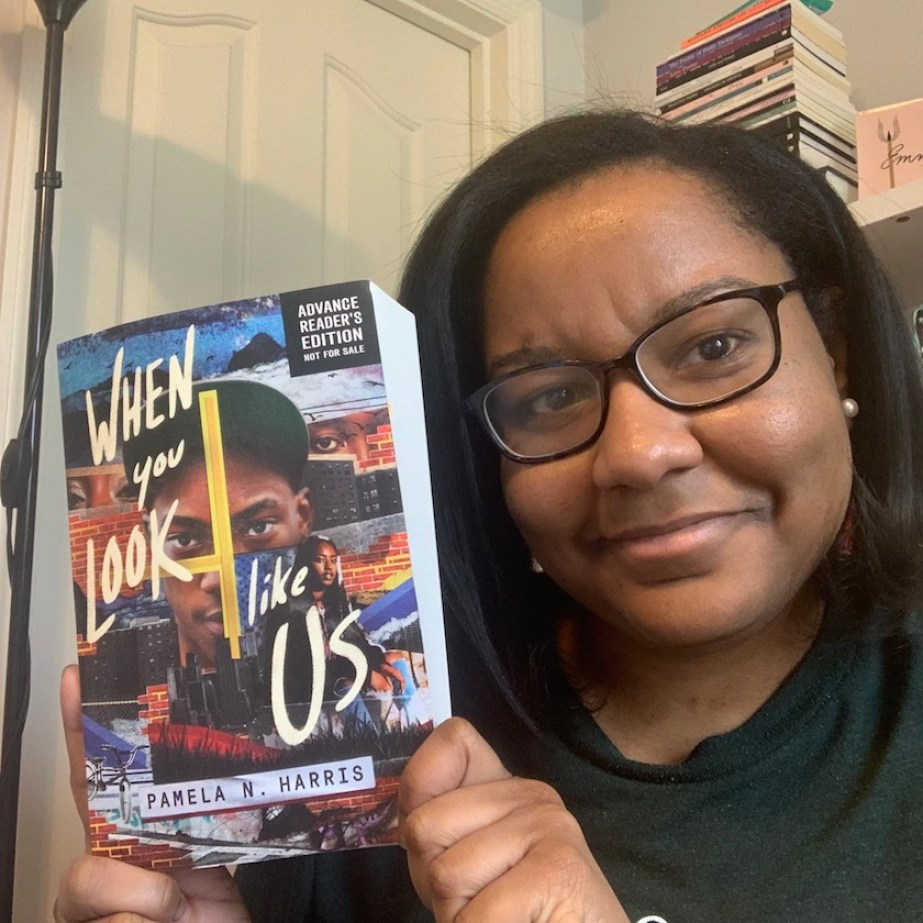 "A woman with glasses holding up a copy of a book titled ""When You Look Like Us."""