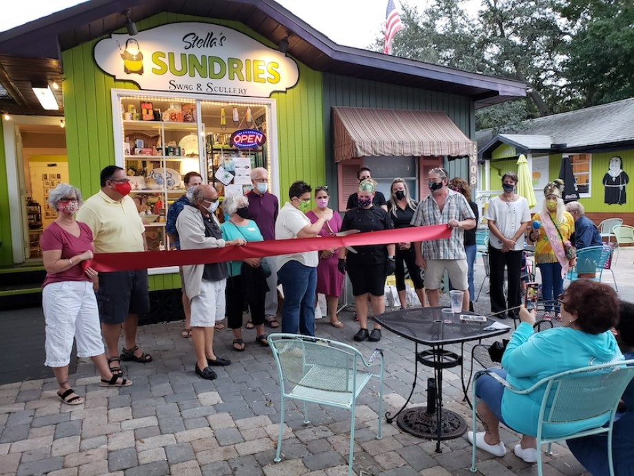 "A group of people gathered under a sign that says ""Stella's Sundries, cutting a grand opening ribbon."