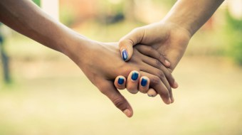 Two people holding hands closeup photo.