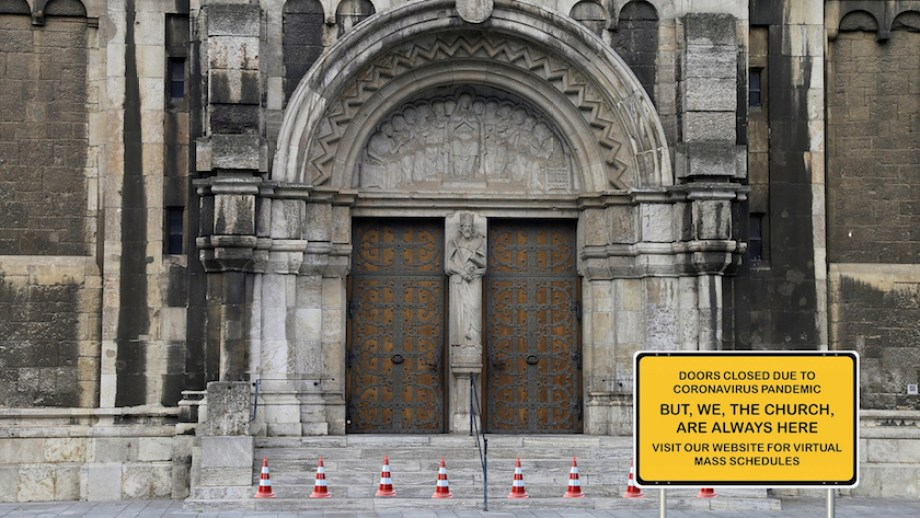 """Doors to a cathedral and steps with a large yellow sign reading """"Doors closed due to the coronavirus pandemic. But we, the church, are always here. Visit our website for virtual mass schedules."""""""