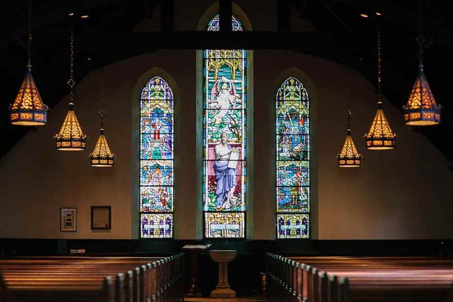 An empty church with three stained glass windows.