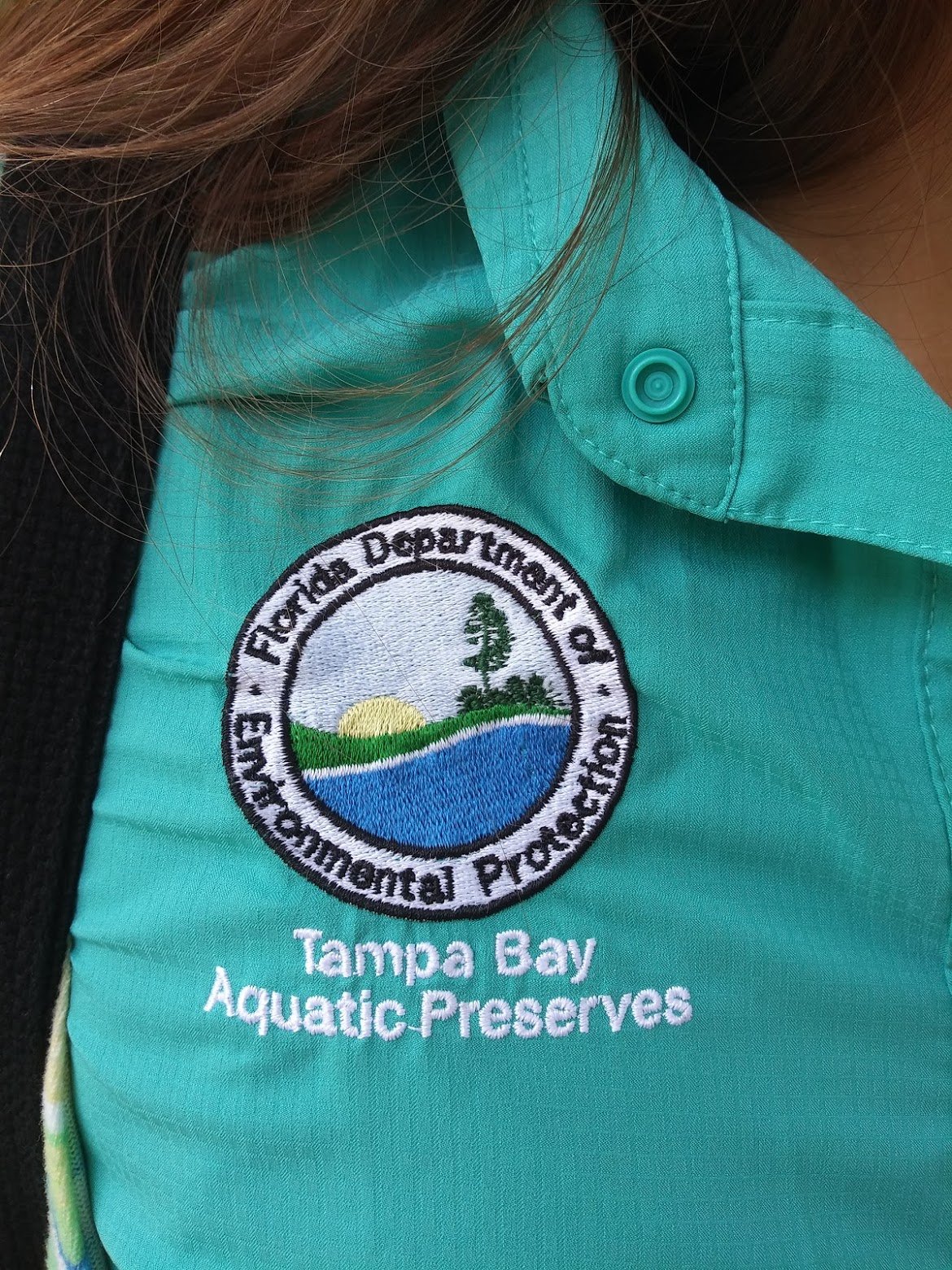 """A closeup of a patch on a green-blue shirt that reads """"Tampa Bay Aquatic Preserves"""""""