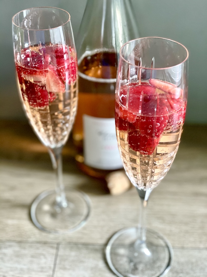 Two flutes of champagne with strawberries floating in them