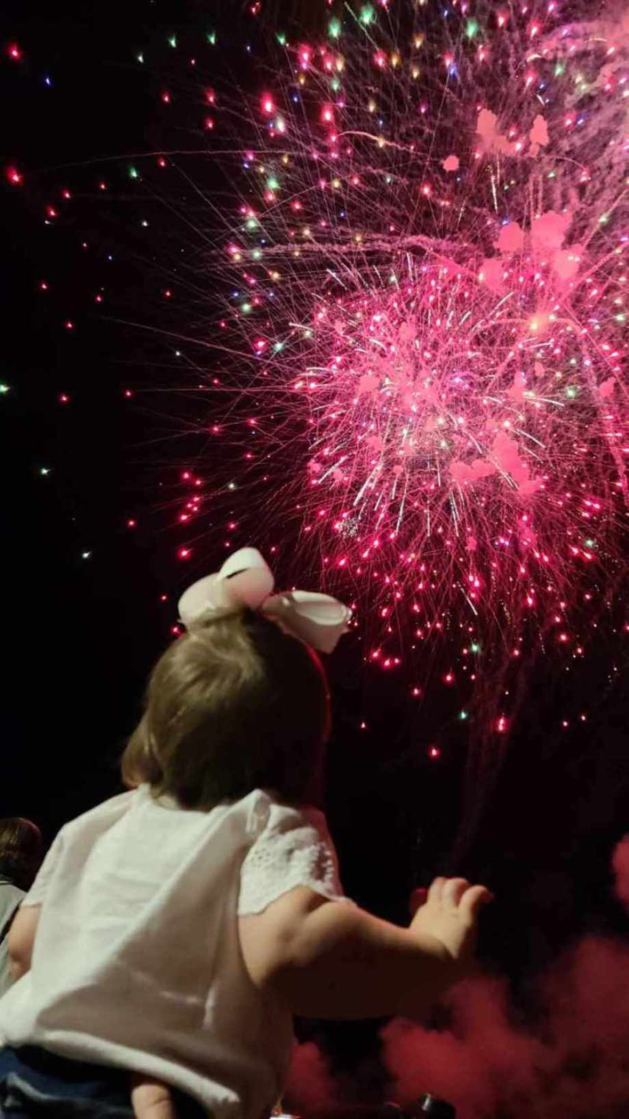 A small child looking up at pink fireworks in a night sky