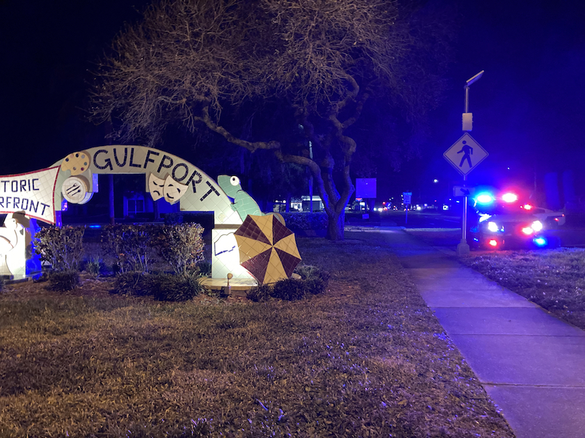 "A night crash scene with blue and red police lights and an artistic street sign reading ""Gulfport Historic Waterfront"""
