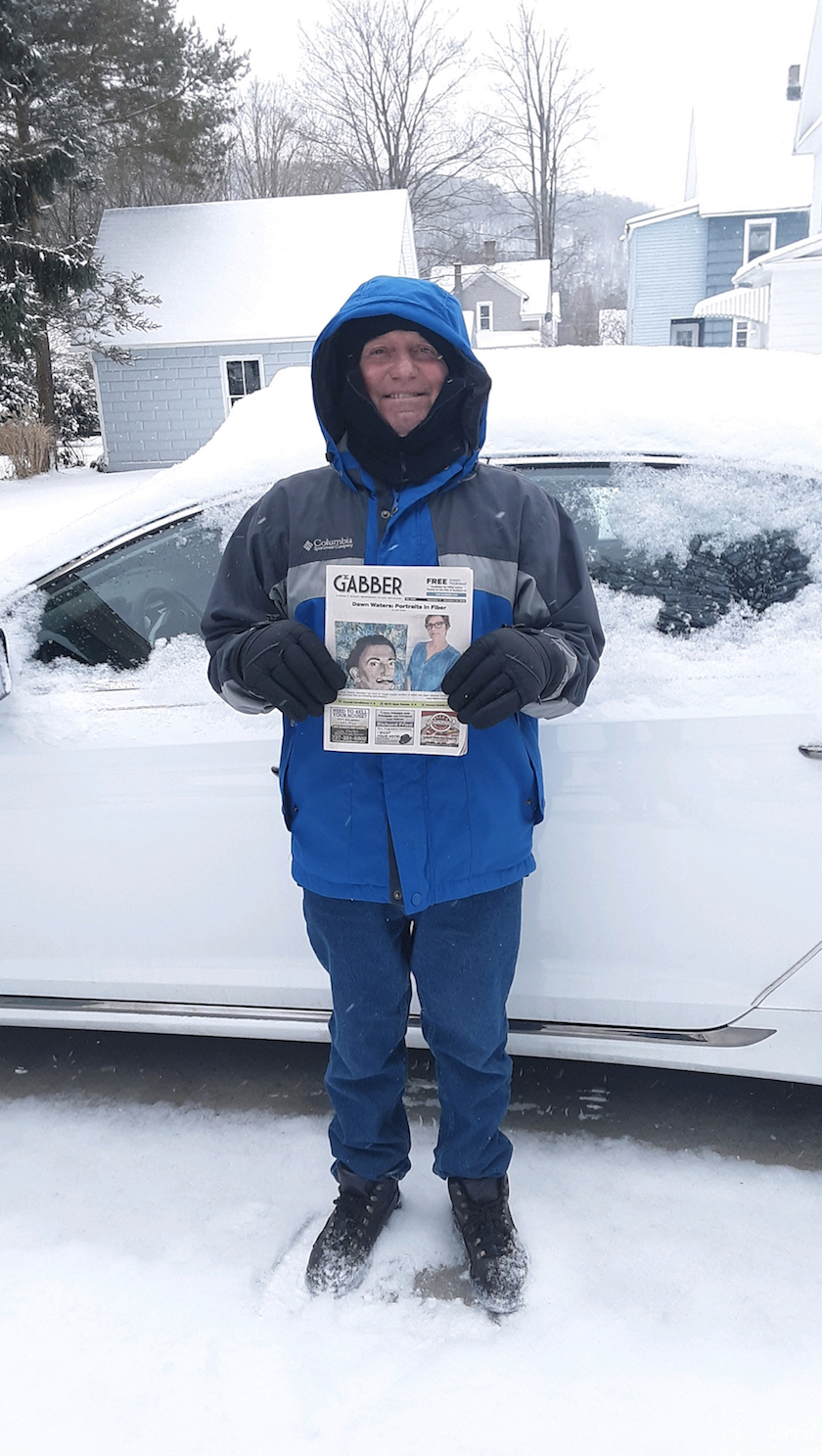 A man standing in snow next to a car, wearing a blue coat and holding a Gabber Newspaper.