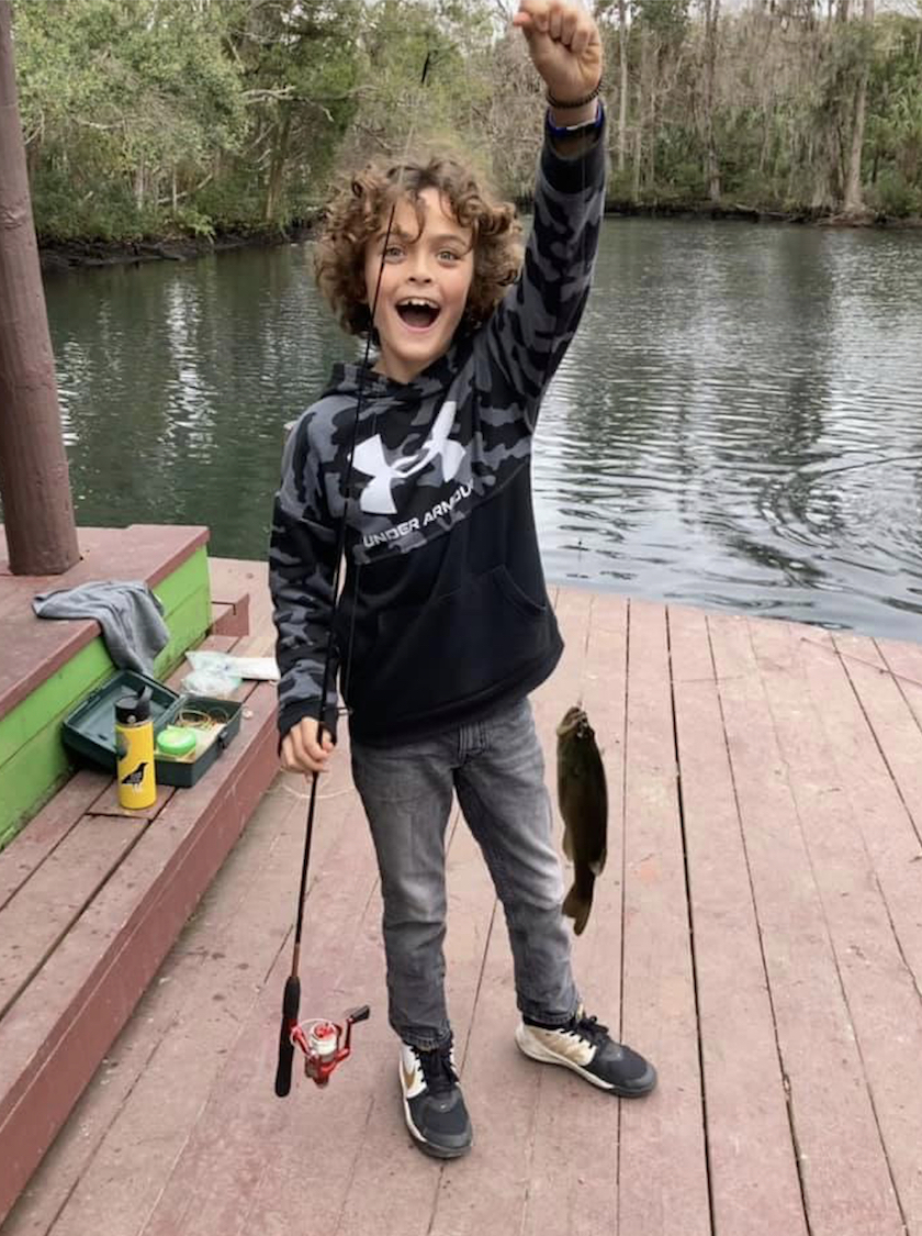 A boy holding up a fishing rod and a fish near the water on a dock