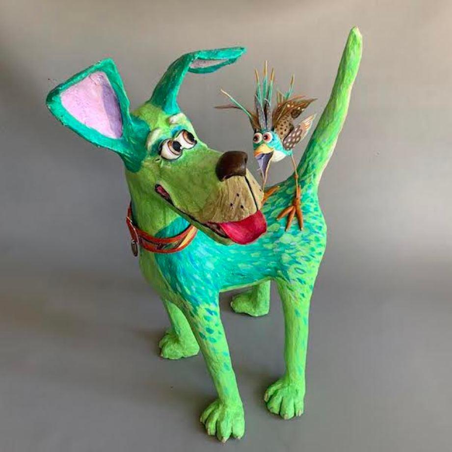 A papier mache green dog