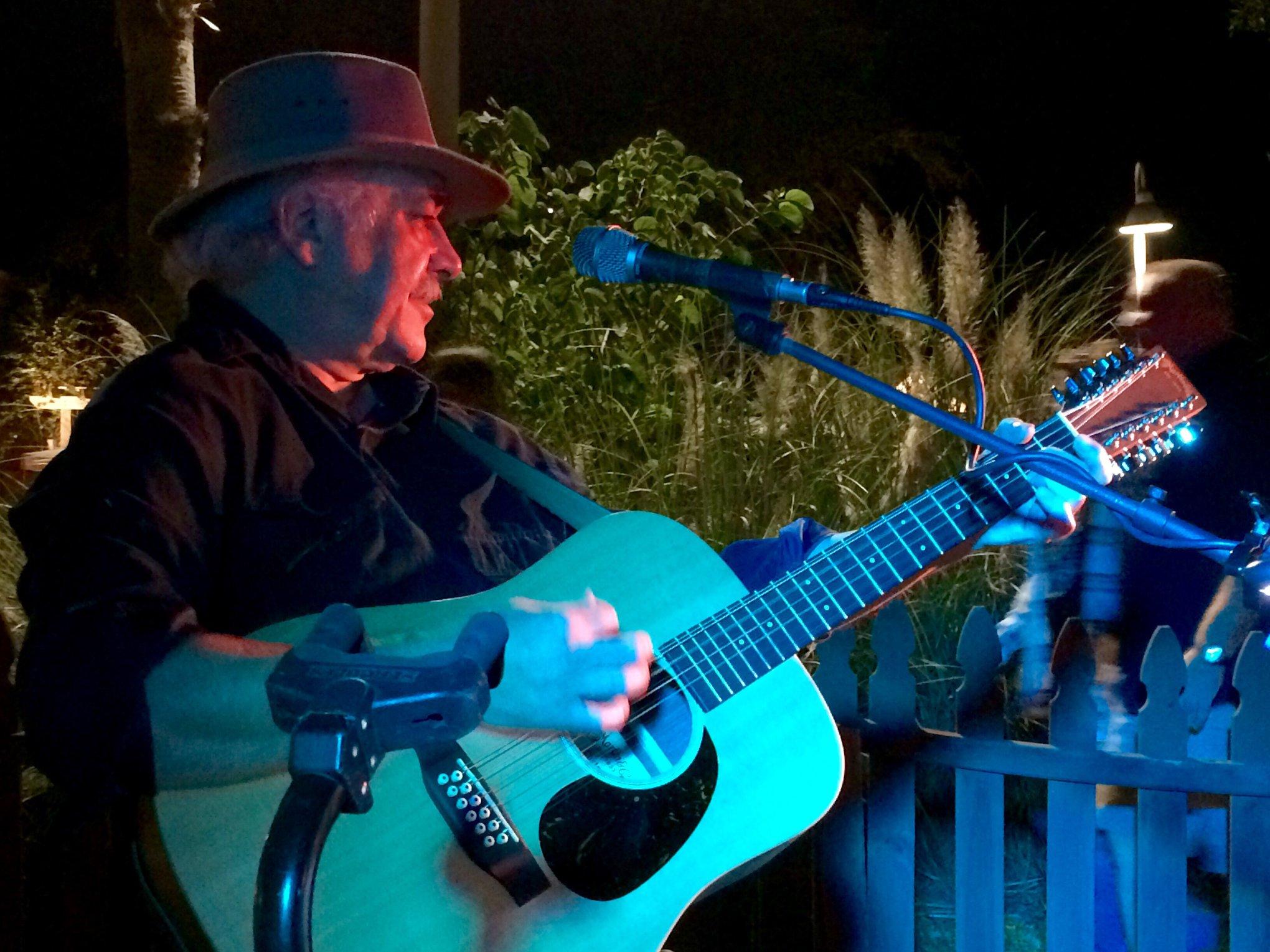 A man playing a guitar in a blue haze of lights.