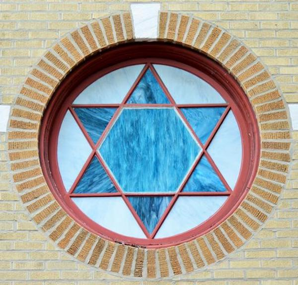 Blue Star of David in a stained glass window form.