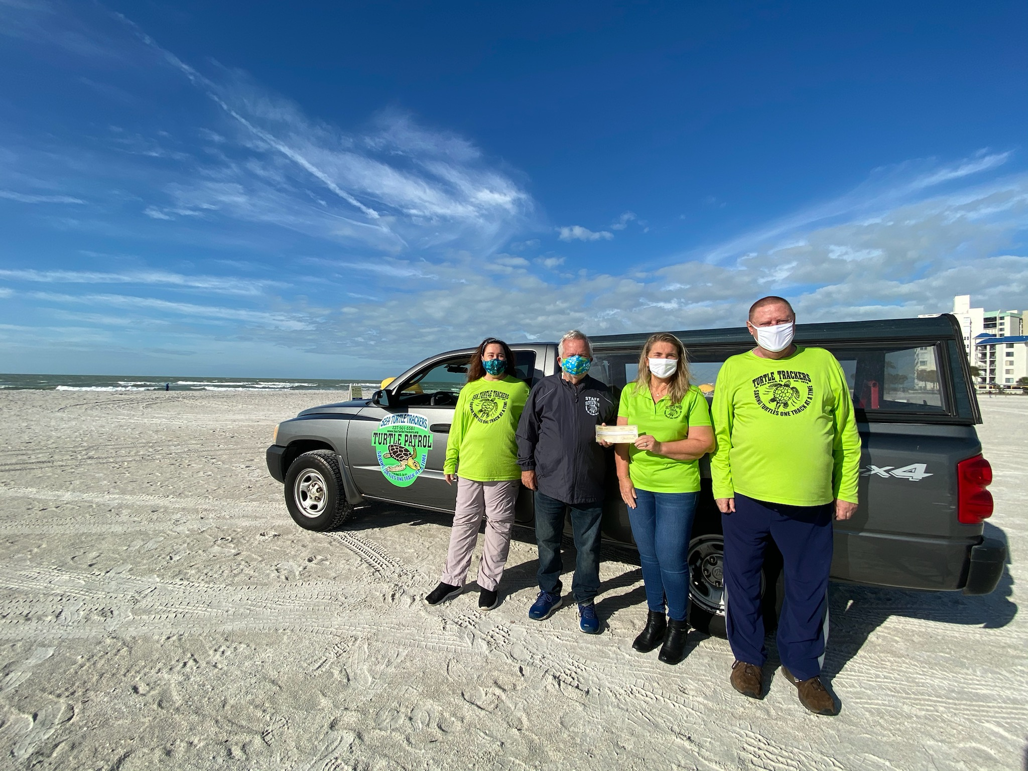 Four people standing next to a dark gray truck on a beach with a blue sky