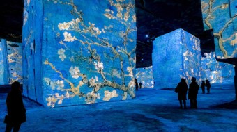 A blue hued room of wall length Van Gogh exhibits. People are walking around the museum