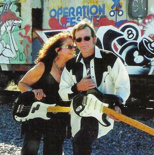 A man and a woman with black and white guitars in a vintage photo.