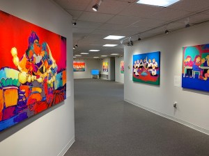 A white-walled art gallery with several colorful paintings hung on the walls.